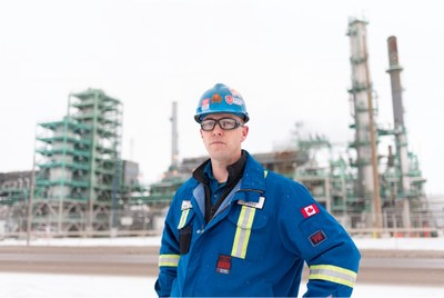 Worker in overalls and hard hat standing outside of a refinery (CNW Group/Unifor)