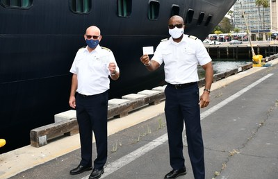 From Left to right, Koningsdam Captain Henk Draper and ship Hotel Director Errol Nelson, hold their COVID vaccine cards in front of Holland America Line's Koningsdam at the San Diego Cruise Terminal. Sharp HealthCare administered COVID vaccinations to the ship's more than 100 crewmembers Wednesday morning.