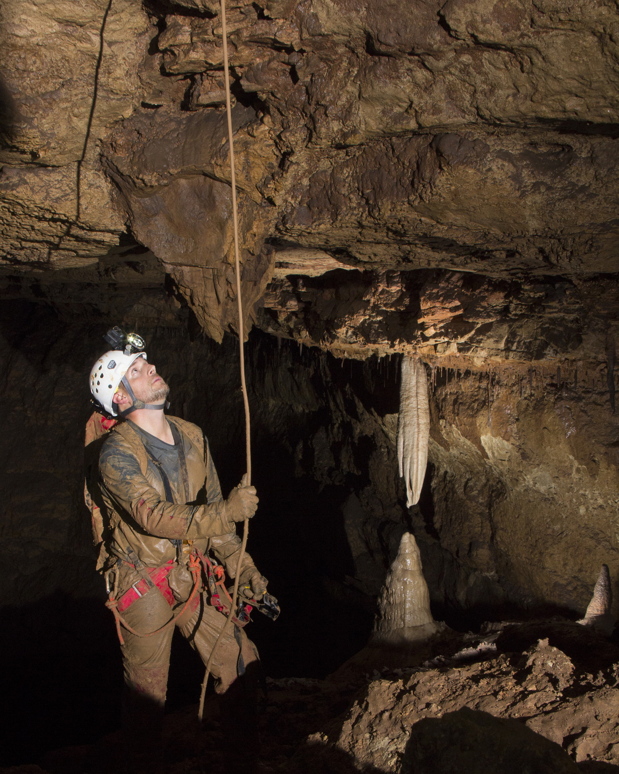 Man in helmet and head lamp looking up towards a stalactite