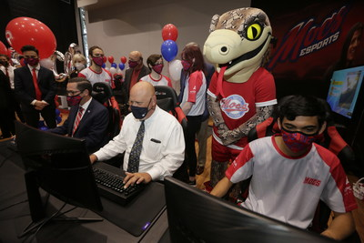Florida Southern College's mascot, Mocsie, watches as Drew Howard, director of athletics and dean of wellness, plays a round of Rocket League with Class of 1990 alumnus and CPS Investment Advisors President and CEO, Peter Golotko, and Mocs Esports player and sophomore Isaac Garay.